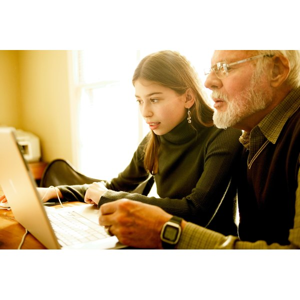 Teenage girl and grandfather using laptop