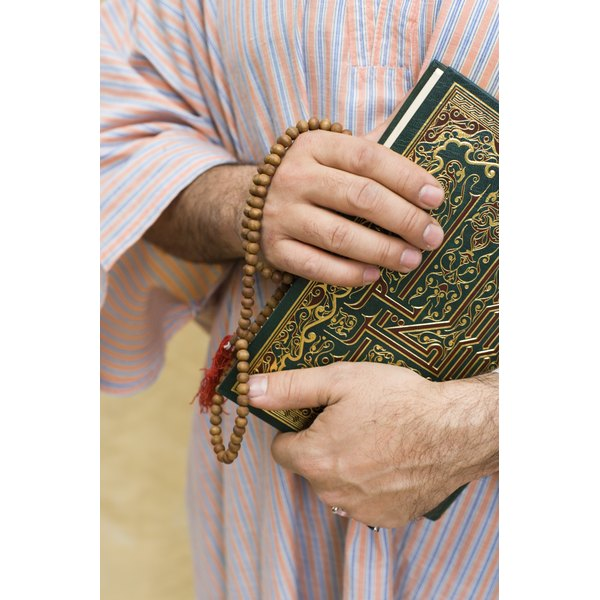 Hands of Middle-Eastern man holding the Koran and Tasbih Prayer Beads