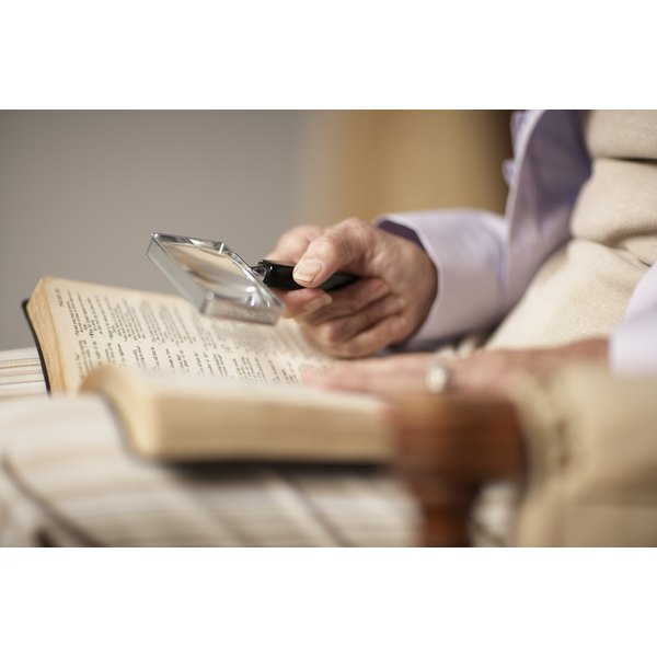 Senior woman reading Bible using magnifying glass, mid section, side view, close-up of hands