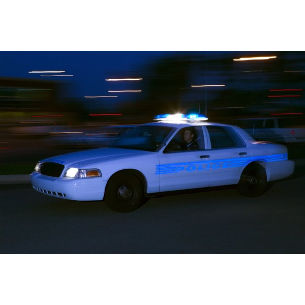 Man driving police car at night