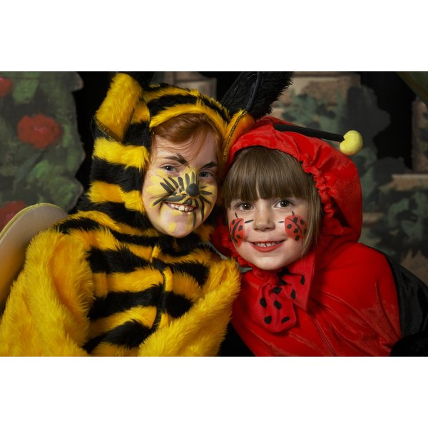 Two girls (6-8) in bee and ladybird costumes, smiling, portrait