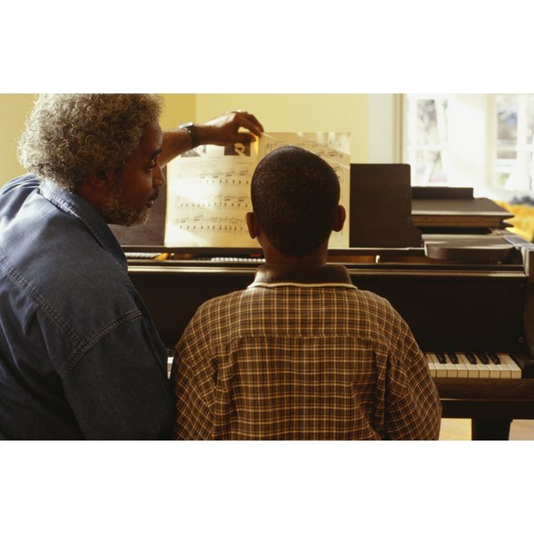 Man giving boy (14-15) piano lessons at home