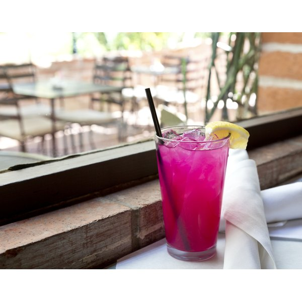 An icy glass of pink lemonade on a table at an outdoor cafe.