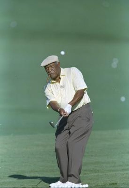 Charlie Sifford, puffing on his trademark cigar, plays a shot during the 1997 Senior PGA Championship.