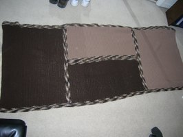 A crocheted lap blanket in two colors with variegated trim