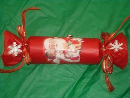 A Christmas party cracker gift, wrapped, decorated and ready to give away.