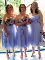 Bridesmaids in tea-length gowns.