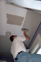 Skimming the plasterboard ceiling in preparation for paint.