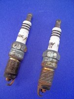 Two used spark plugs with badly worn electrodes