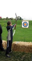 Archers use bows to shoot arrows at targets.