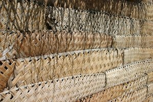 Palm leaves are woven to make thatch panels for a roof.