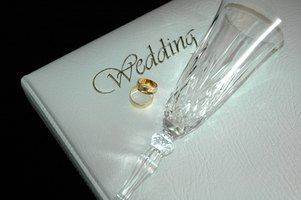 A wedding sign-in book with ring and toasting flute.