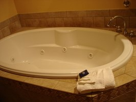 A whirlpool tub is installed in an enclosure
