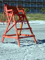 Lifeguards often sit on elevated chairs to improve the visibility of the swimming area.