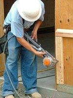 Carpenters use nail guns to frame walls.