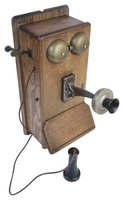 Antique wooden wall phones feature call bells and side cranks.