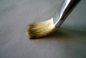 A stiff-bristled brush works best when applying acrylic varnish.