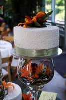 Decorate a small wedding cake with cornelli lace and top with flowers.