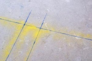 Chalked lines on a concrete floor serve as a guide for placing tiles.