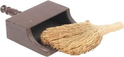 Remove crumbs and debris from the Klobo sofa with a broom and dustpan.