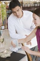 Restaurant managers review receipts with employees.