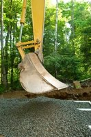 Excavators can be used to spread rock over drain field pipe laterals.
