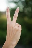 "Two fingers raised in a ""V"" symbolize peace."