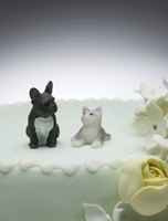 A small dog decorates the top of a cake.