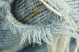 Frayed edges around ripped knees of blue jeans are fashionable again.