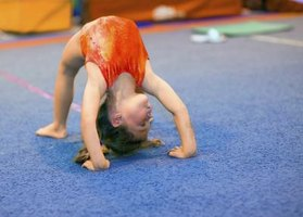 Small child doing bridge in gymnastics class
