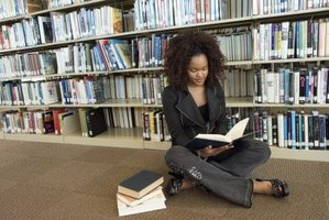 Young student studying in library with pile of books by her side