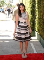 Actress Nina Dobrev pairs gray sandals with a dress in black, white and shades of gray.