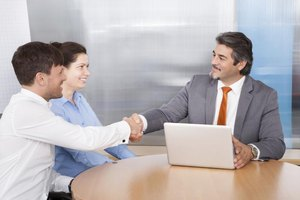 Insurance agent shaking hands with young couple