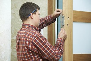 A locksmith replaces a door lock.