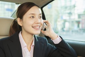 Businesswoman on a cellphone in the back of a car.
