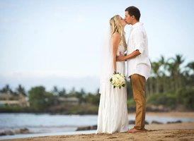Bride and groom kissing on a beach.