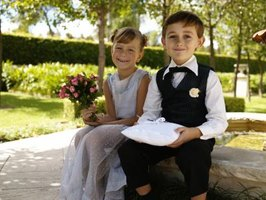 A flower girl and ring bearer sitting on a bench.