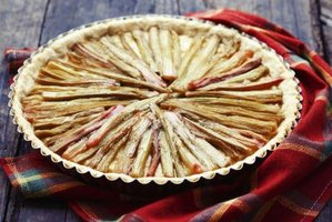 Roasted rhubarb arranged in a pie crust on a rustic table with a plaid cloth napkin.