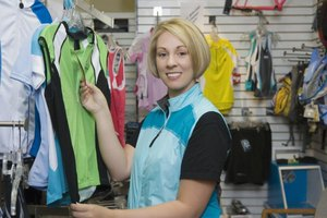 Woman in sporting apparel store choosing a Dri-FIT top.