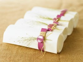White napkins in a pink ring decorated with a sprig of beach grass.