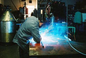 A welder works in his shop.
