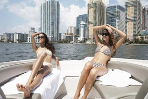 Two women wearing bikinis lounge on a boat in Miami.
