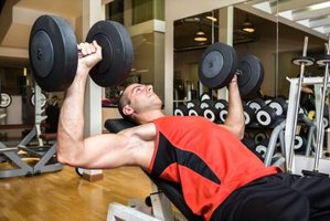 A man lifting weights with his arms in a gym.