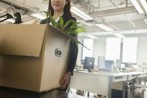 Woman leaving office with box of personal items