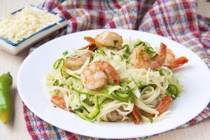 Shrimp served on a bed of pasta and zucchini ribbons topped with freshly grated parmesan cheese.