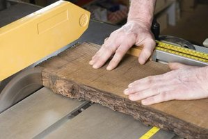Close-up of man cutting hardboard with table saw