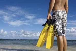 Man holding fins while standing on a beach.