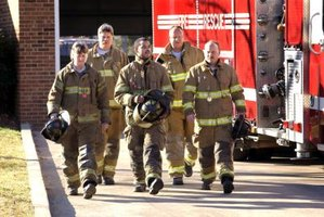 A pack of firemen walking out of a station.