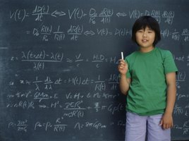 Student holding chalk in front of board with math problems