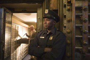 A security guard stands in front of a vault of safety deposit boxes.